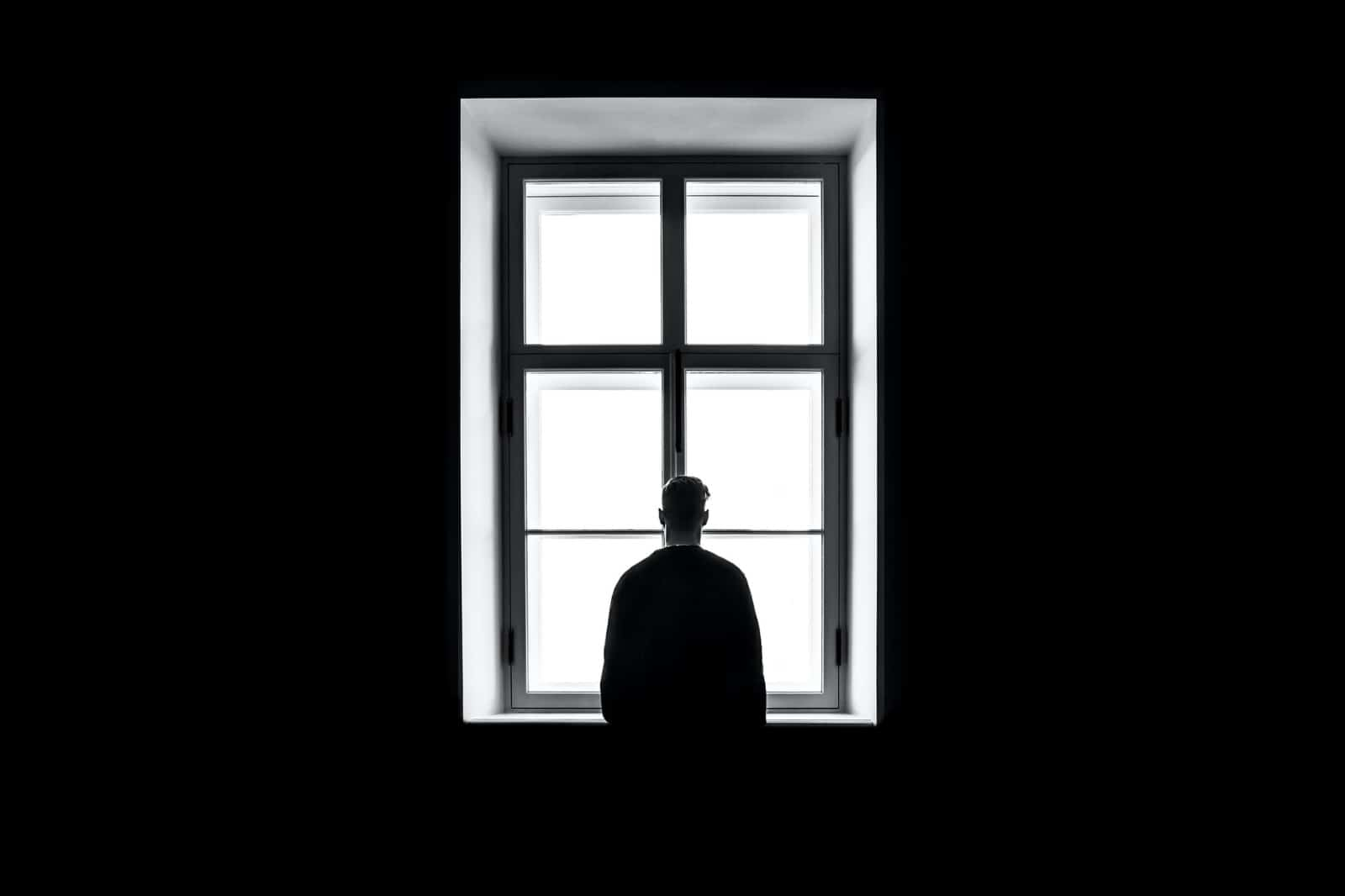 Man with depression looking at the window